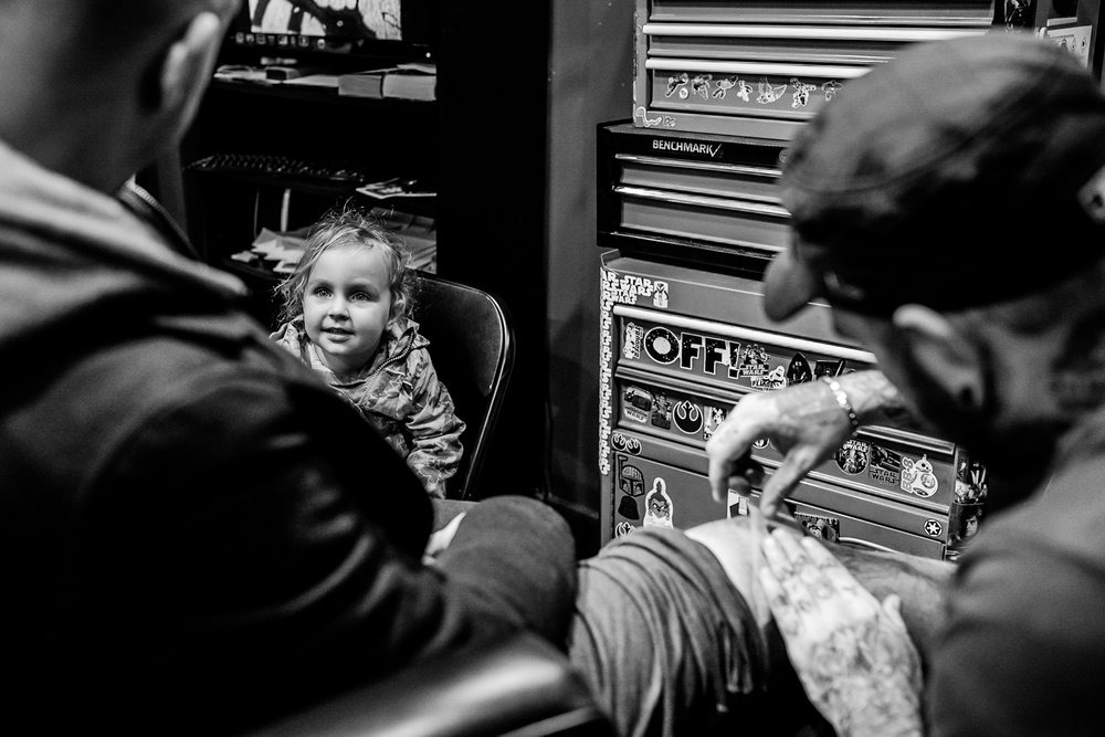 Little girl looking at dad getting a tattoo
