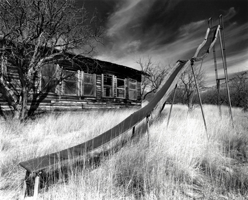 Ron Rigge  The slide , 2007 Toned silver gelatin print 10.5 x 13.5 inches  I have been photographing as well as printing my own work for over 25 years.  Today my major interests are found compositions of old signs and weathered buildings, relics of a recently passed civilization. While my photographic methods have changed over the years, I feel the most important issue is not the technique or new technology used but the strength and emotion in the image. In the last few years I have been fortunate to share my work in both group and one-person shows.  I look forward to photography as a lifelong avocation. -Ron Rigge