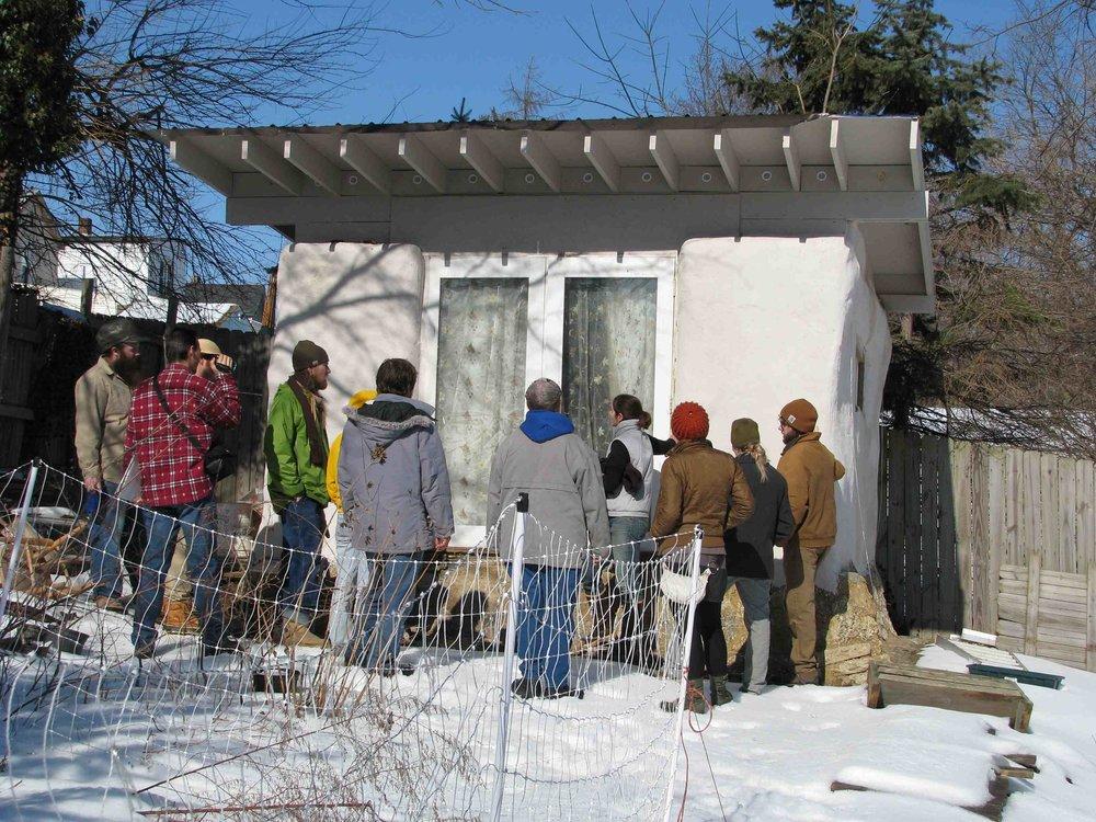 Students visiting a load baring passive solar strawbale shed