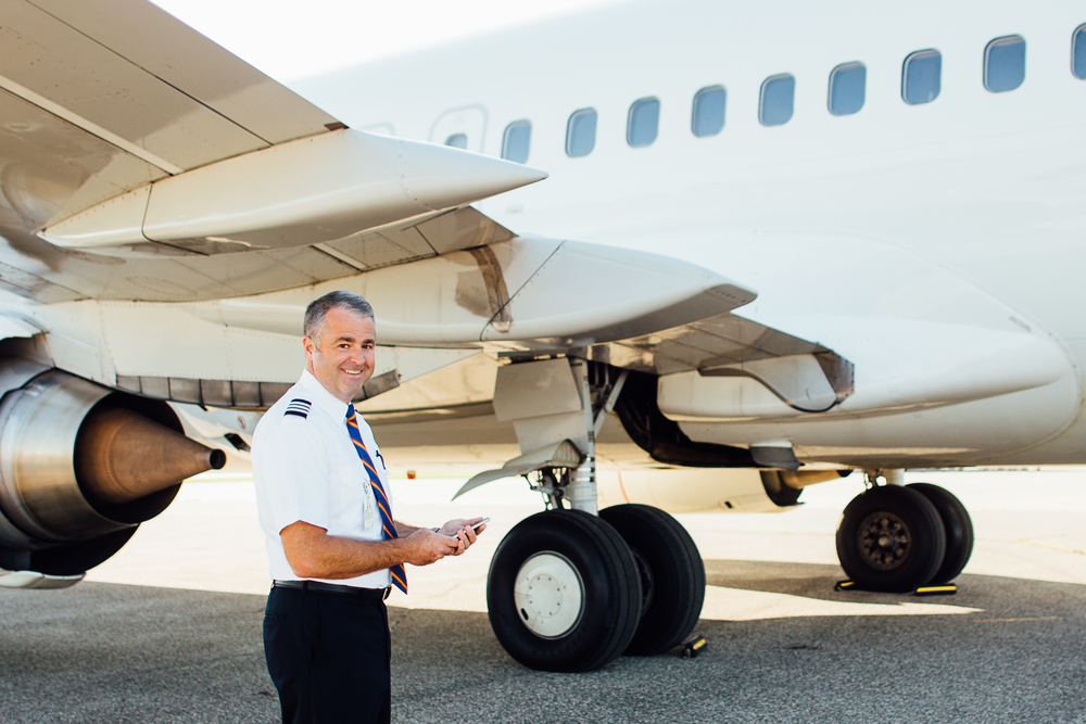 pilot smiles next to plane at Kalamazoo/Battle Creek International Airport