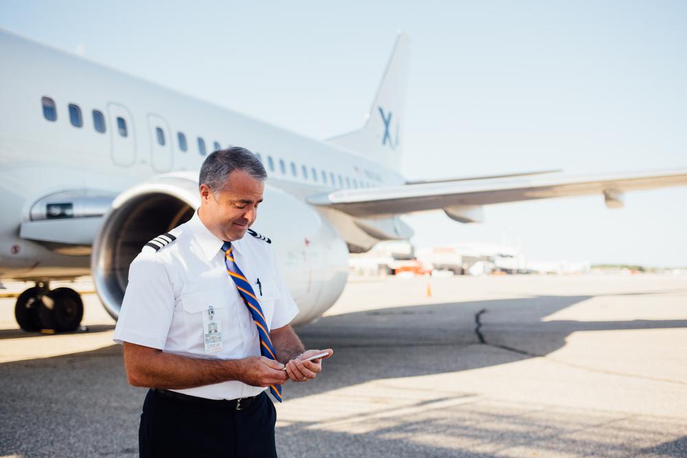 pilot using phone by plane at Kalamazoo/Battle Creek International Airport