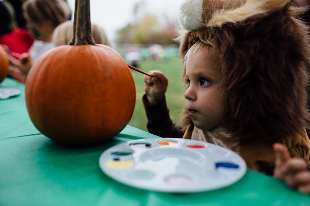 young boy in lion costume painting pumpkin at fall festival