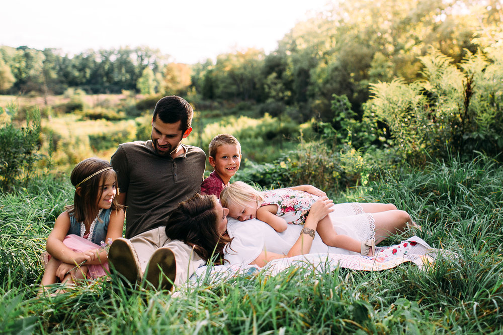 family snuggling in tall grass at sunset
