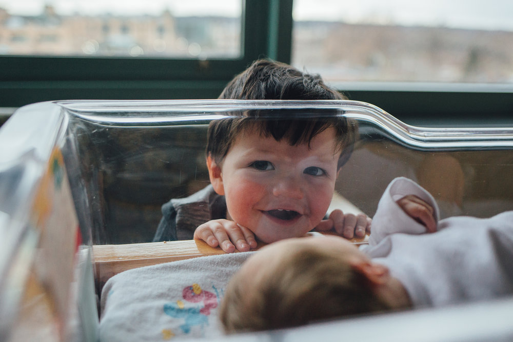 boy looking through baby crib in hospital