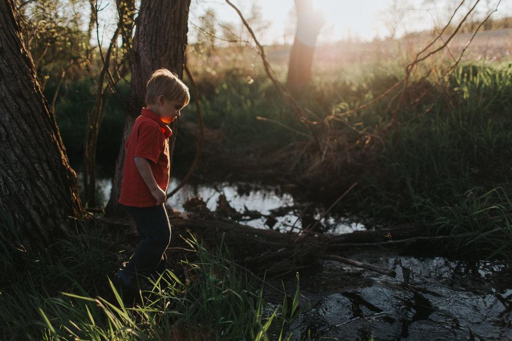 boy walking on log by creek