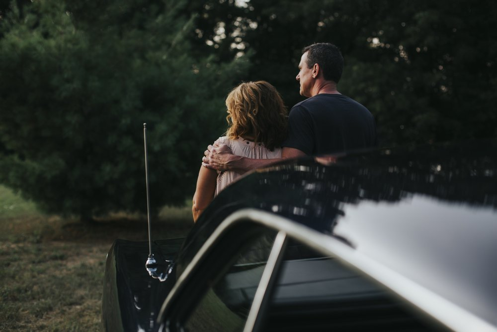 couple leaning against old car