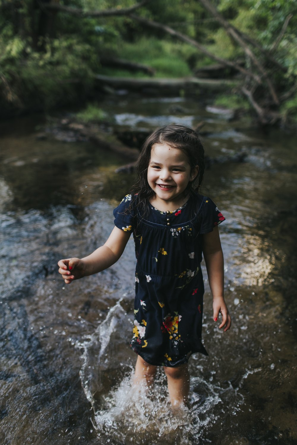 little girl splashing in creek