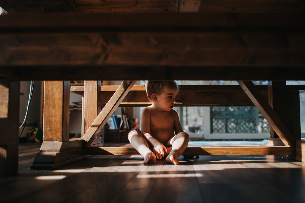 boy sitting under table in the afternoon sun
