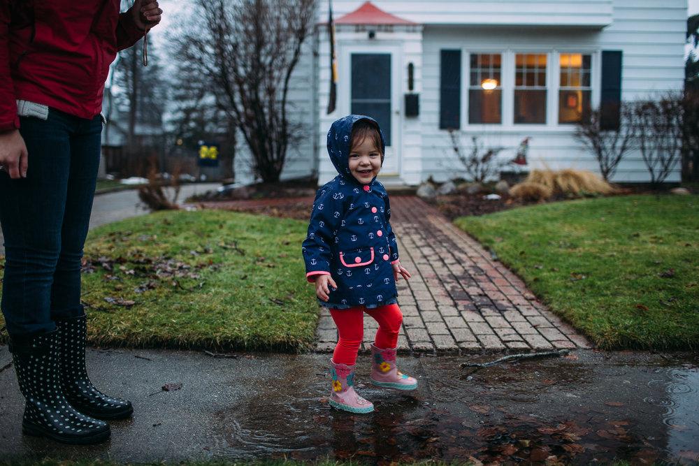little girl splashing in puddles by home in kalamazoo michigan