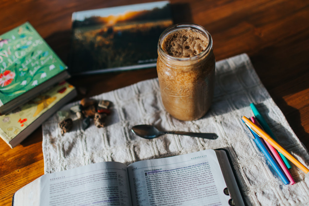 frothy mocha shake sitting on table surrounded by bible, nature books, and pens
