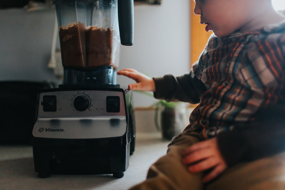 little boy pushing vitamix blender button
