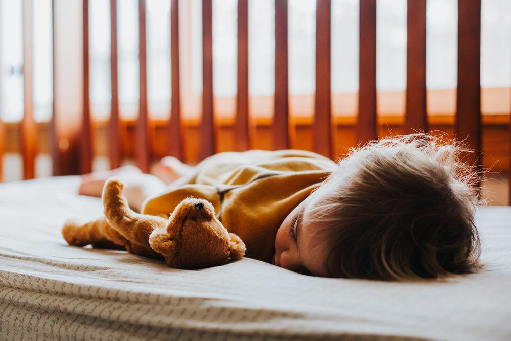 toddler boy sleeping in mahogany crib with teddy bear