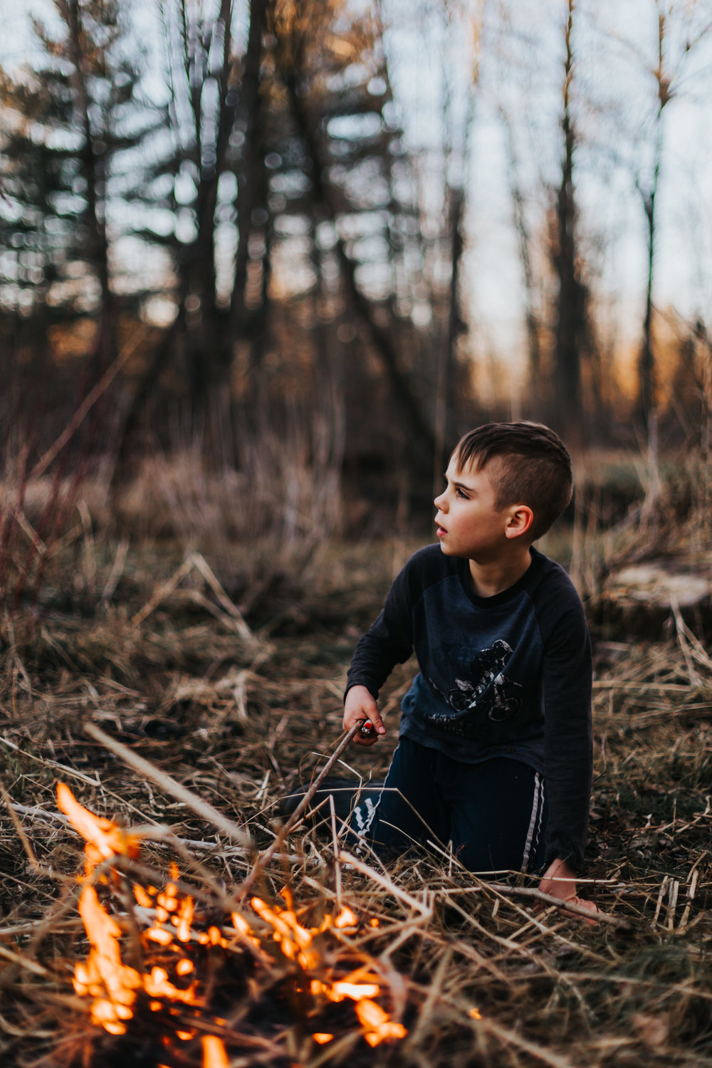 young boy lighting a fire in tall grass