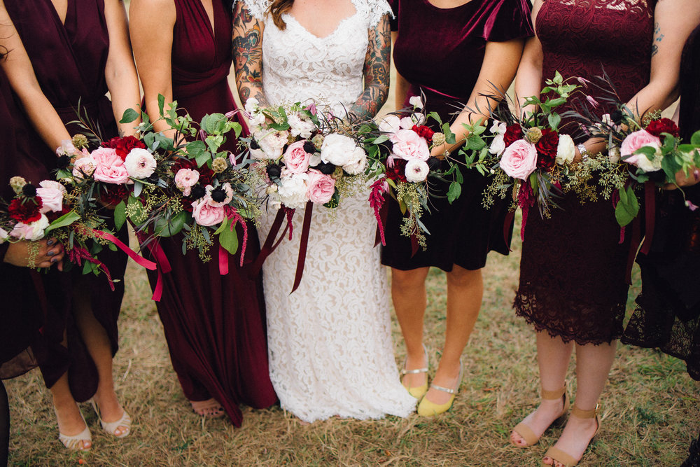 Moody bridal and bridesmaid bouquets in burgundy and blush with peonies, garden roses, ranunculus and seeded eucalyptus. Photo by Chance Reaves, Revelia Studios,