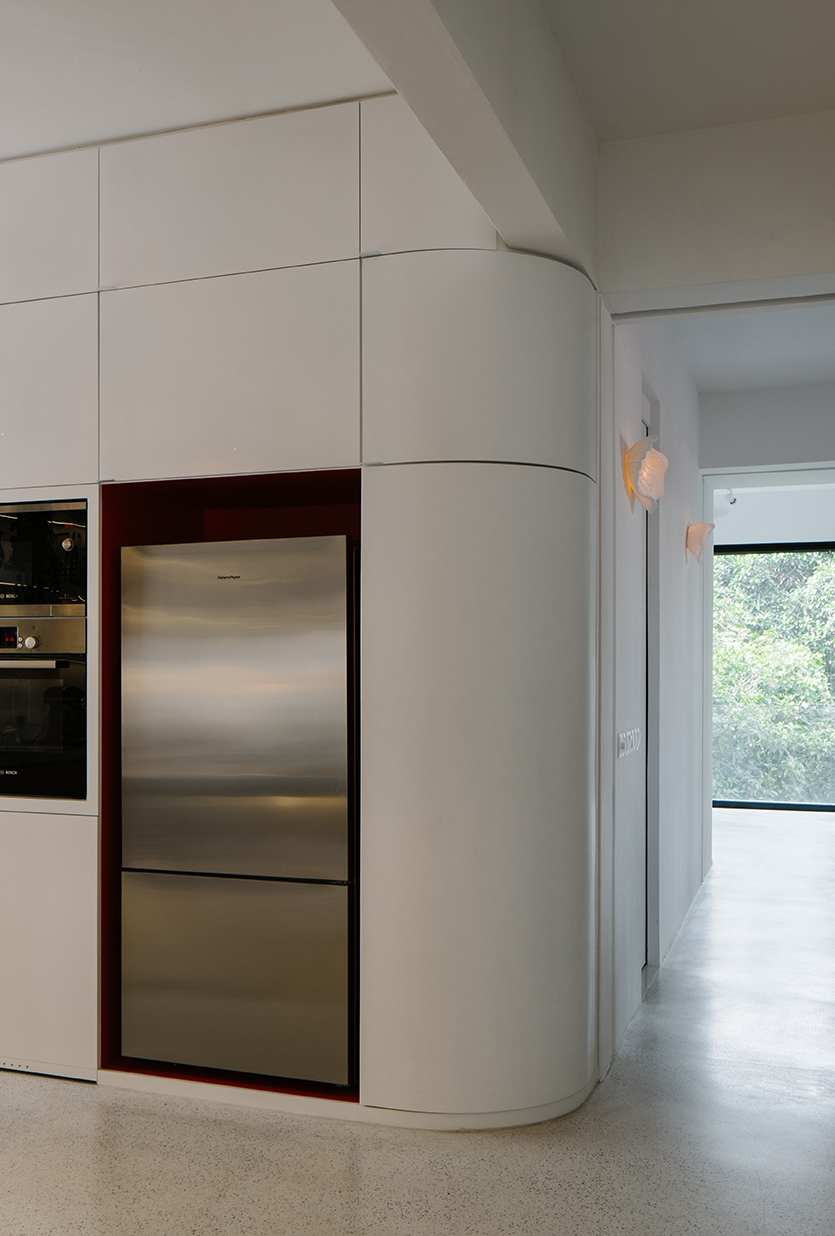 The curved cabinetry softens the transitions between each space, drawing the occupants through the apartment.