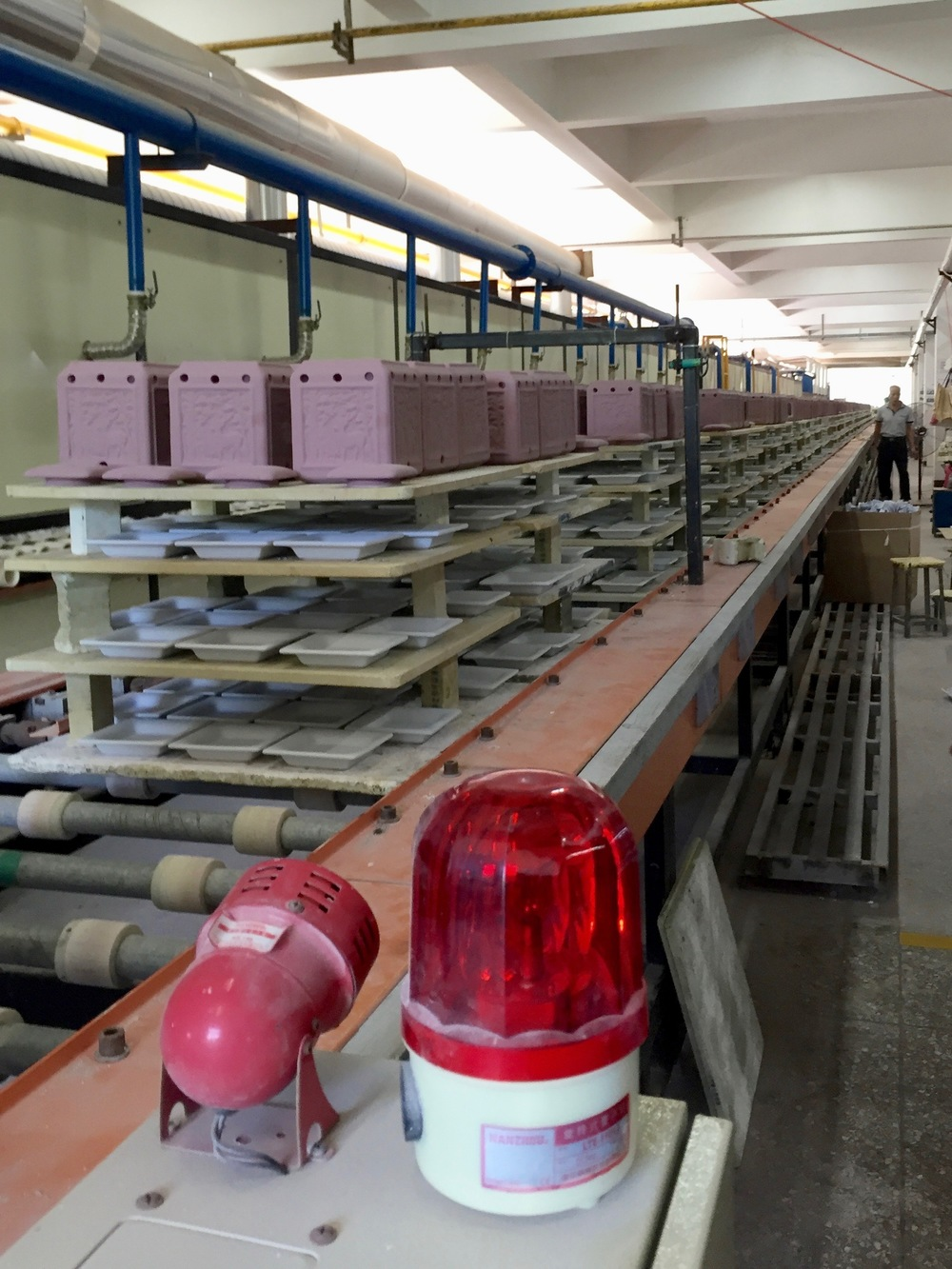 This is a computerized kiln that is continuously moving. It takes about 8 hours for one piece to move through the entire kiln. What you see here is a long conveyer belt where ceramic items are stacked onto the shelves. The shelves move on this conveyer to the end, they make a u-turn, and then enter the kiln.