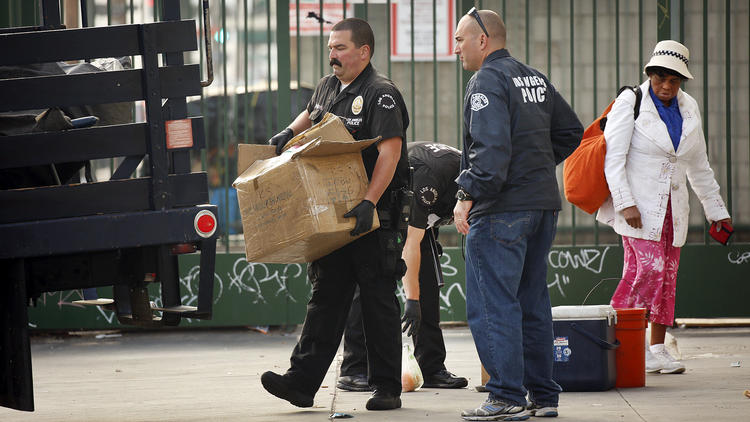 Members of the LAPD confiscating personal property on Skid Row.    (photo via   Los Angeles Times  )