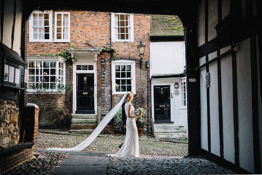 Bride walking down mermaid street in Rye