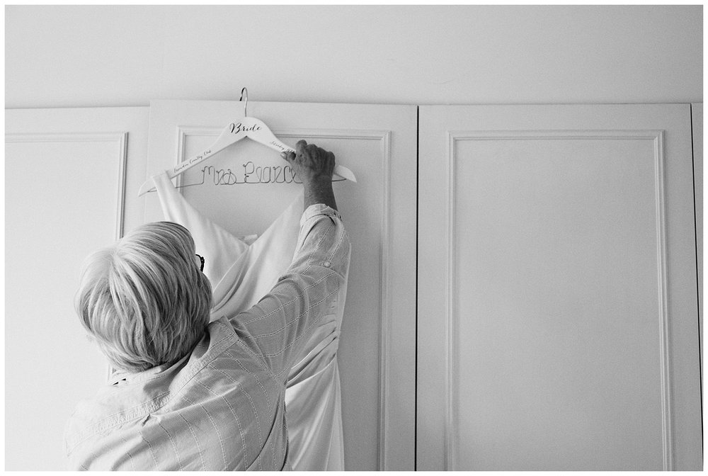 mother of bride hanging dress on wardrobe during bridal preparation in Winchmore hill
