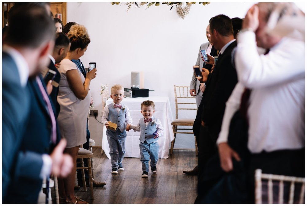 two cute page boys walking up the aisle during the wedding ceremony at the granary in fawsley