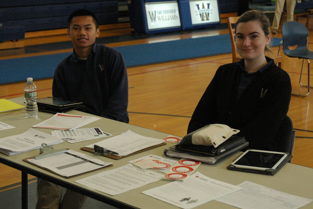 Seniors William Hua and Anna Egan are ready to register the 48 donors at the Red Cross drive held in the gym.