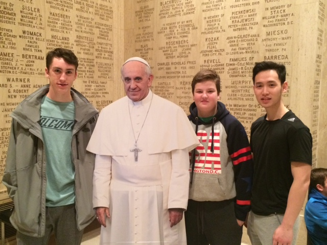 POPE IN SPIRIT: From left, Collin Driscoll '21, Noah Dembrowsky '21, and Luan Nguyen, pose with a life-size poster of Pope Francis at the Basilica of the National Shrine of the Immaculate Conception, Washington, D.C.