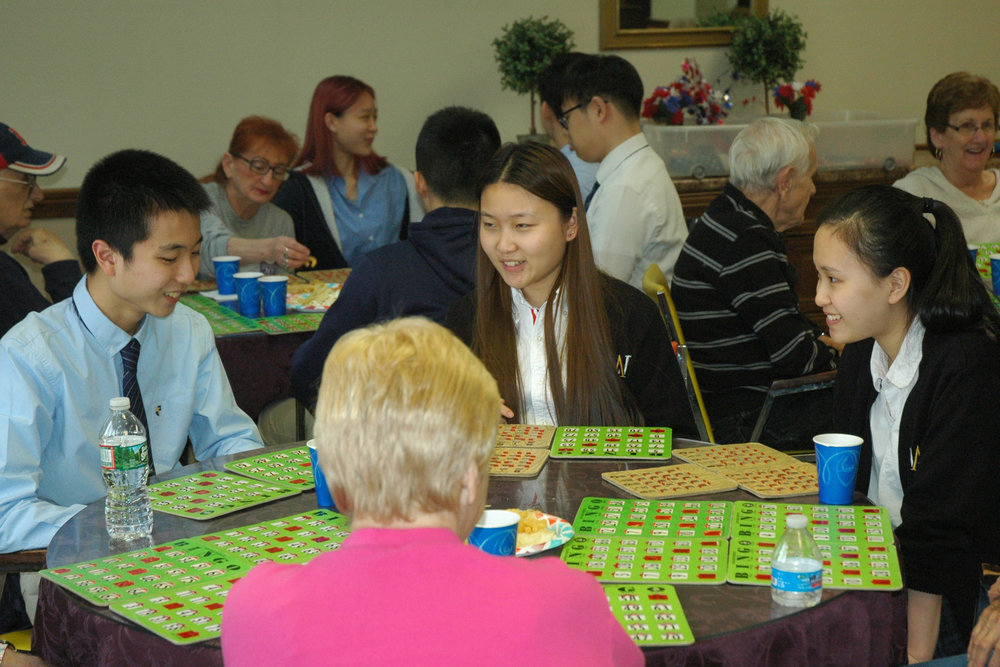 Senior Alex Chen, left, is joined by senior Agnes Liu, center, and junior Wendy Yuan for a Bingo game with senior citizens at Independence Manor.