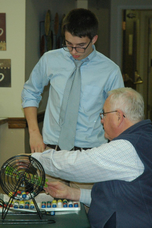 Freshman Andrew Berman checks a Bingo card with caller and Archbishop Williams High School Guidance Counselor Ron Homer.