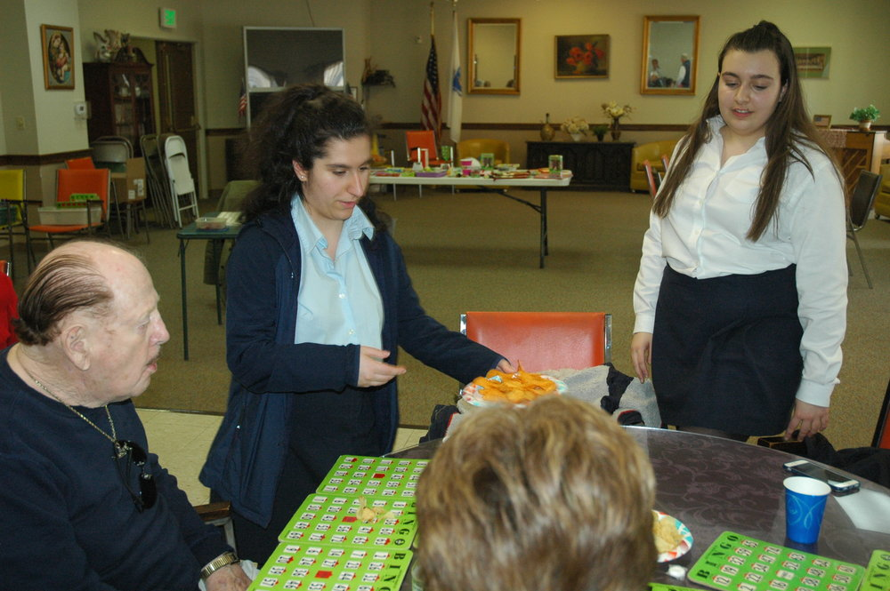 Sophomores Ashley Hamparian (left) and Olivia Raneri serve snacks and drinks to senior citizens at a Bingo game held at Independence Manor.