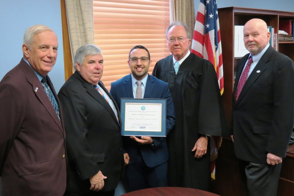 """Emil Ata, Class of 2005, center, an Assistant District Attorney for Norfolk County, will be reporting to Ft. Benning, Ga., for basic training with the Army Reserve, and then to the Judge Advocate General's (JAG) Legal Center and School in Charlottesville, Va. District Attorney Michael Morrissey was presented with the """"Above and Beyond"""" Award by the Department of Defense for supporting Ata and other staff in the military. From left, DoD representative John Pelose, Michael Morrissey, Emil Ata, the Hon. Daniel O'Malley, and DoD representative Leland Dingee."""