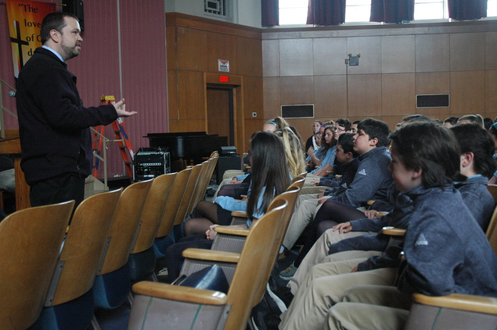Campus Minister David Gilpin discussed homelessness and introduced speaker on the topic.
