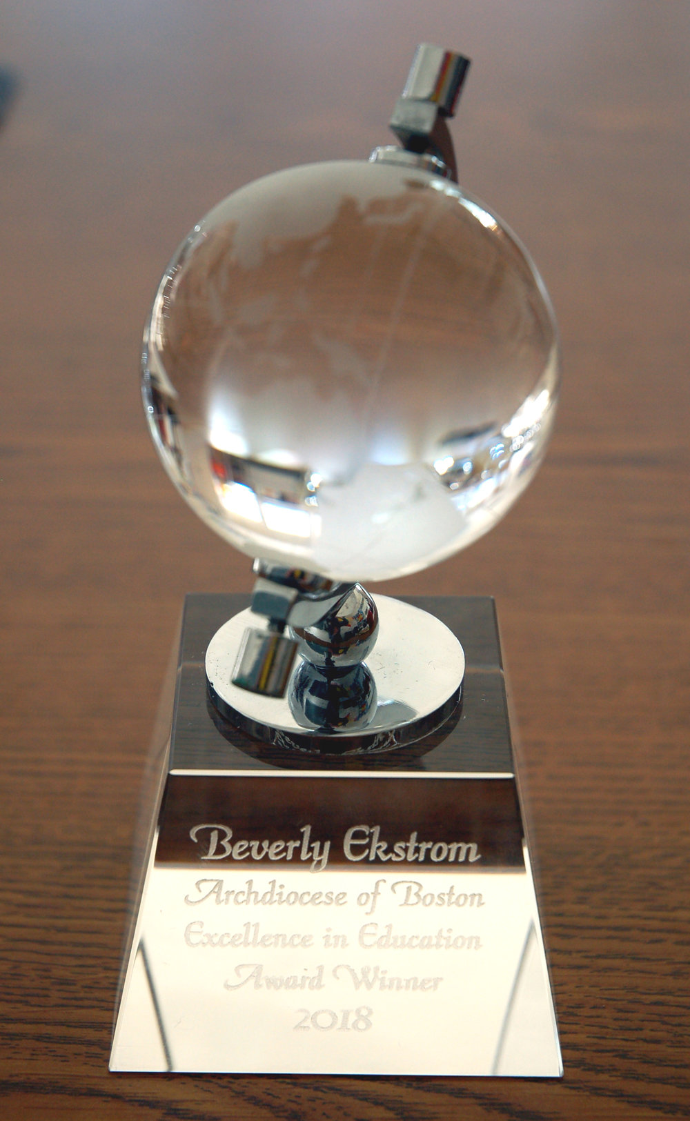 "The base of a glass globe was inscribed with ""Beverly Ekstrom Archdiocese of Boston Excellence in Education Award Winner 2018."""