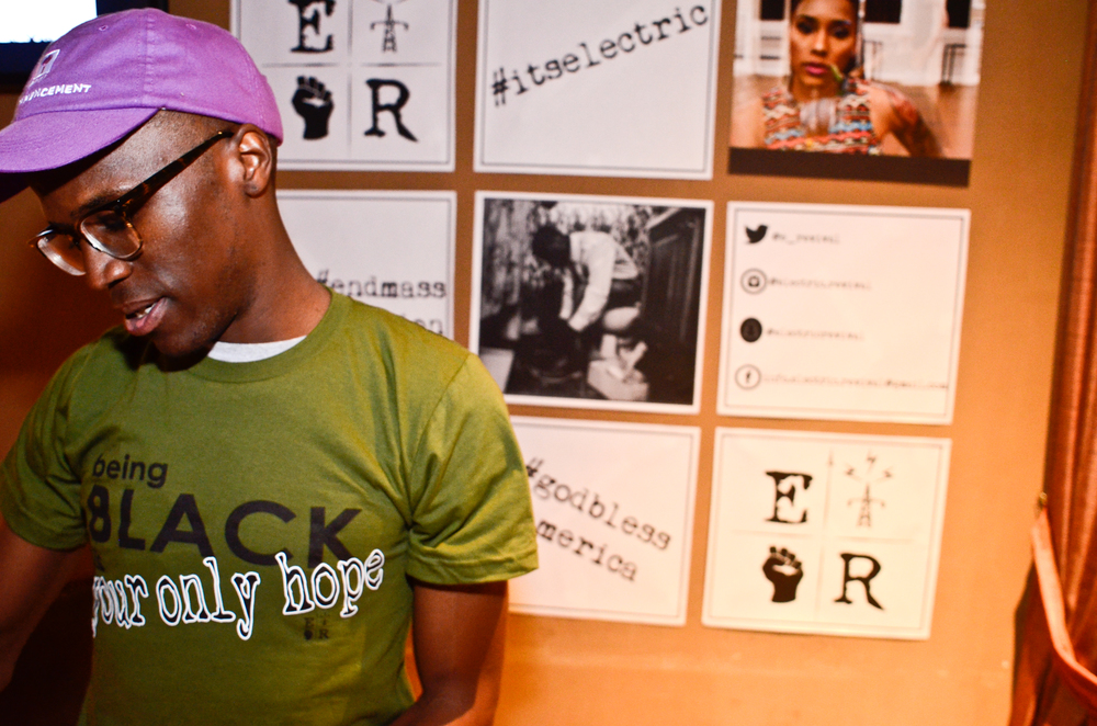 Electric Revival Co-Founder, Terron Ferguson, poses in front of customized Step & Repeat.
