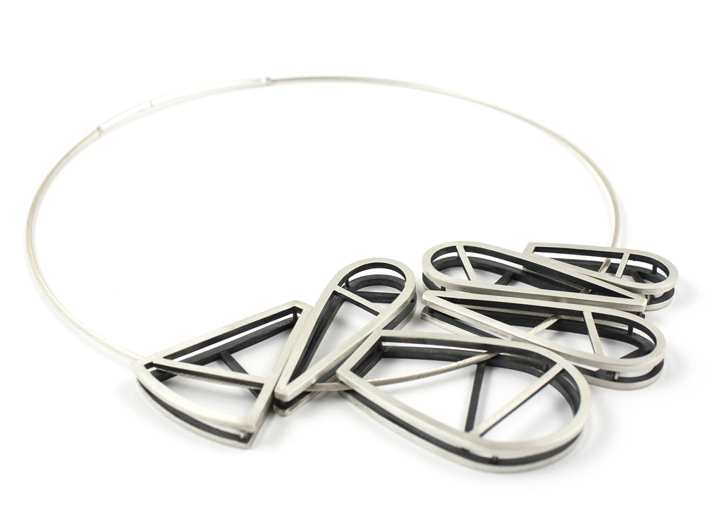 This new statement piece is full of layers and lines. Shapes can flip and move as the wearer pleases. Argentium and sterling silver.