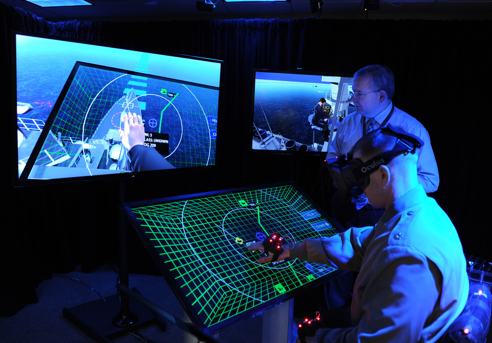 ARLINGTON, Va.  - Jim Blesse, standing, from the Office of Naval Research (ONR), explains project BlueShark to Lt. Col. John Moore from the Marine Corps Warfighting Laboratory. Project BlueShark is an ONR effort to create a high-tech, futuristic environment to demonstrate what operational work environments might look like and what emerging innovative technologies might provide in the next decade.