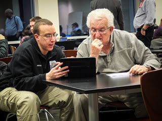 Founder of the Air Force photojournalism program Ken Hackman, right, offers advice during the Visual Media Workshop in Arlington, Va.