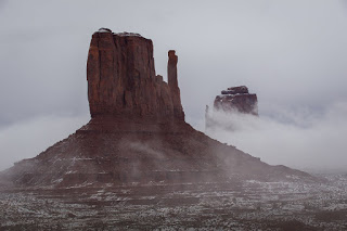 The West and East Mitten become visible as the fog clears after a mid December snow in Monument Valley, Ariz.