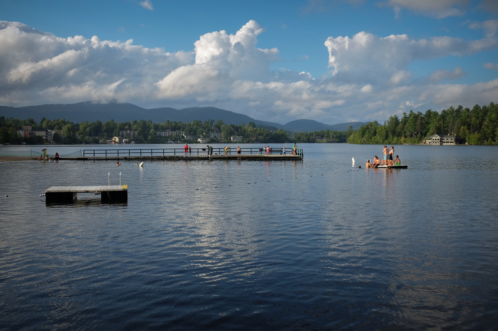 The early evening light highlights swimmers at the public beach on Lake Mirror located in Lake Placid, N.Y. 1/300 @ f8, ISO 200.