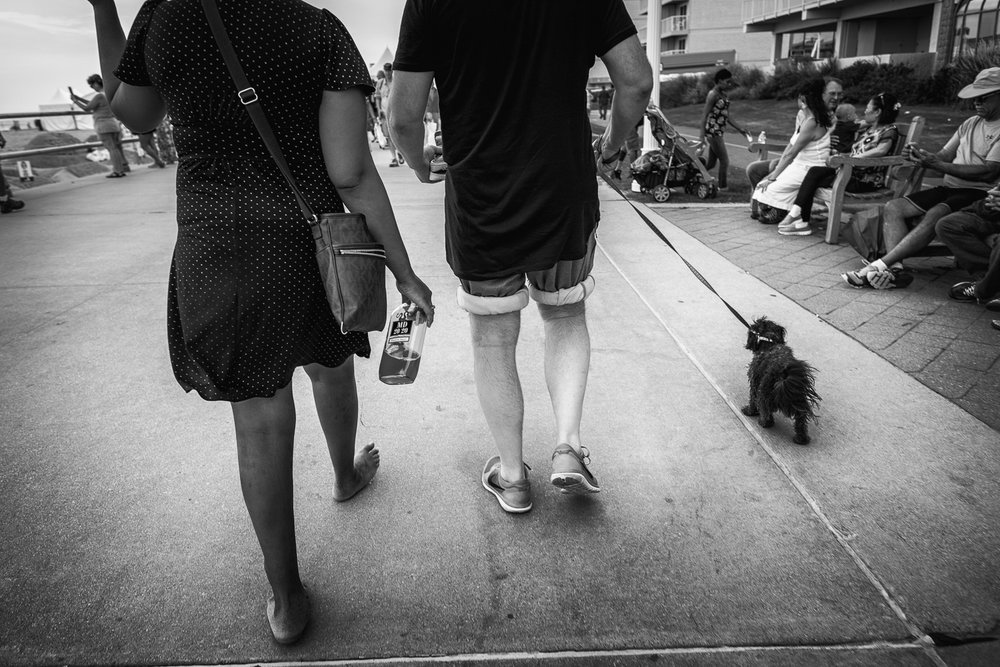 The first thing I noticed was the bare feet and the half empty bottle of liquor as this couple approached me on the boardwalk in Virginia Beach. That was enough for me to turn around and follow. When I noticed the dog, I had all I needed for an interesting photograph. I followed for about five minutes before the crowd thinned enough for me to isolate those elements.  Fujifilm X-Pro2 with a 16mm, 1/340 @ f2.8, ISO 200 .