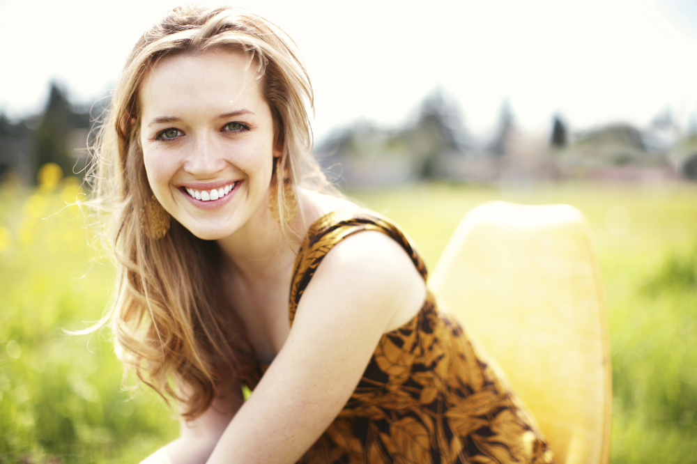 Smiling blond girl sitting outdoors