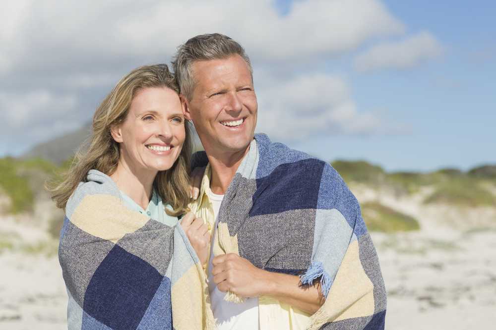 middle age couple wrapped in blanket on the beach