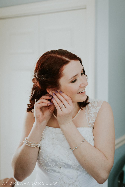 bride_putting_on_earings_wedding_day_ct_wedding_photographer.jpg
