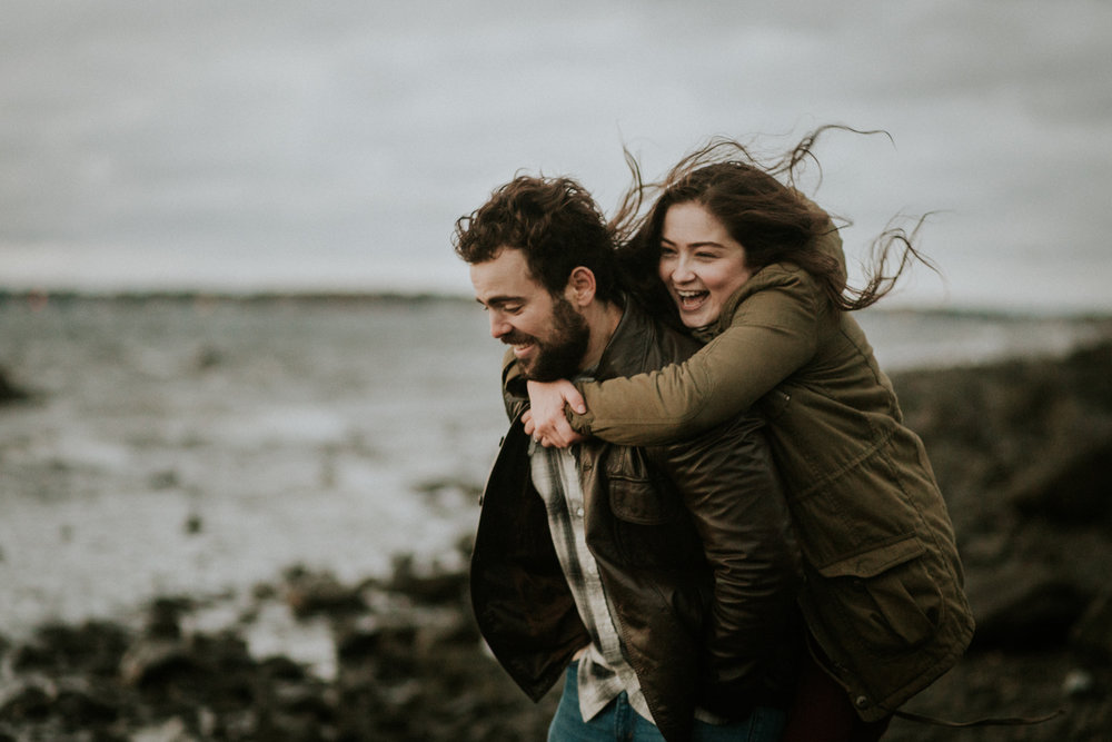 piggyback_wind_hair_leather_beach_colt_state_park_leather_jacket_parka_engagement_outfit_adventure_outdoors_trees_dress_outdoors_connecticut_rhode_island_massachusetts_new_england_wedding_photography_photographer_natural_laid_back_fun_light_engagement_session.jpg