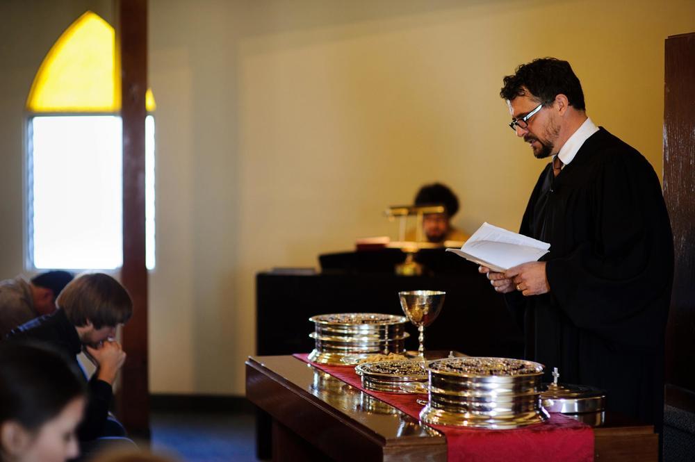 Rev. Michael Brown conducând congregația în închinare prin intermediul formulei liturgice în timpul oficierii sacramentului Cinei Domnului la  Biserica Reformată Unită din San Diego .