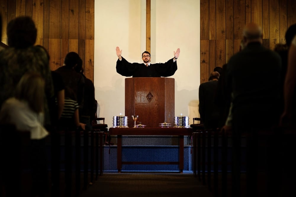 Rev. Michael Brown rostind benedicția de la finalul liturghiei la Biserica Reformata Unita din San Diego, California.