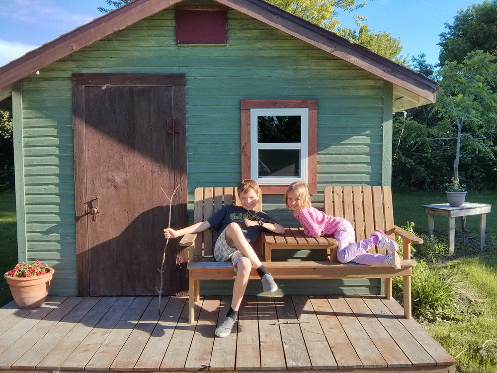In front of the chicken coop, turned playhouse