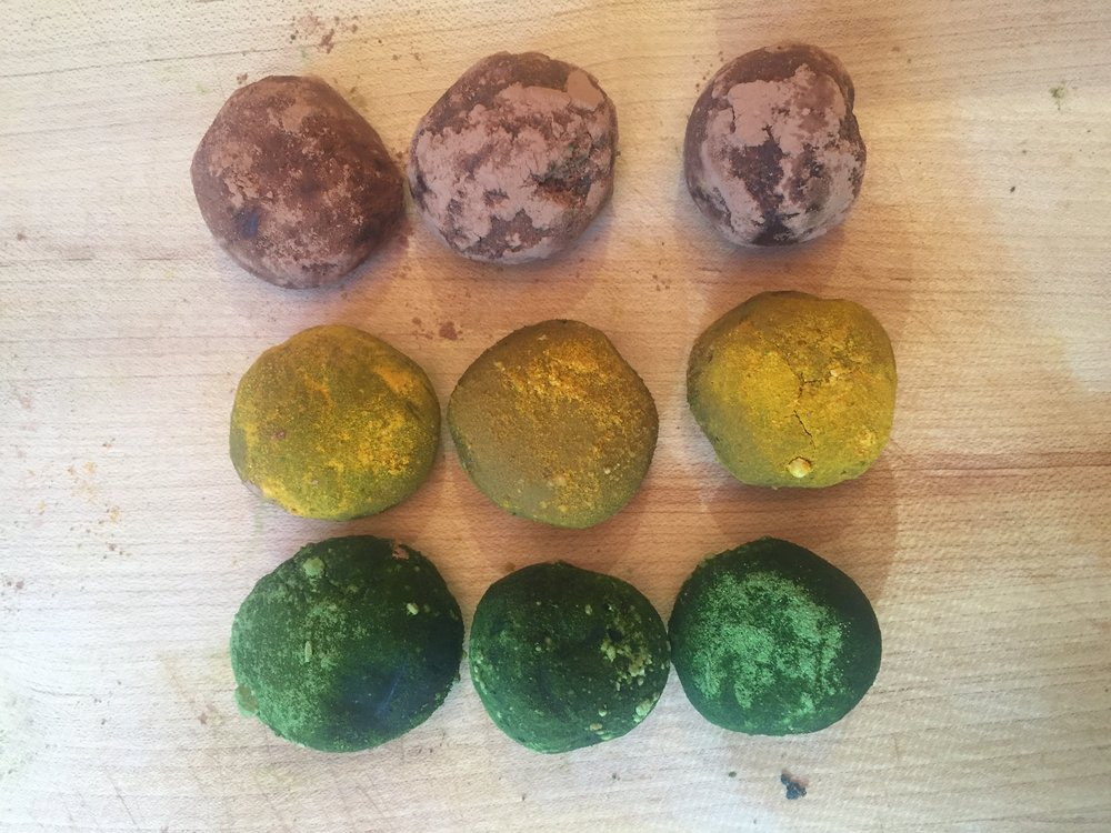 Raw vegan cacao truffles coated with three different coatings: (top) cacao powder , (middle) turmeric & coconut sugar powder and (bottom) matcha & coconut sugar powder coating.