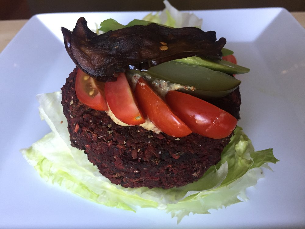 Beet, kidney bean and mushroom  burger,on a lettuce bun,topped with a piece of eggplant bacon, pickles, tomato, and avocado.
