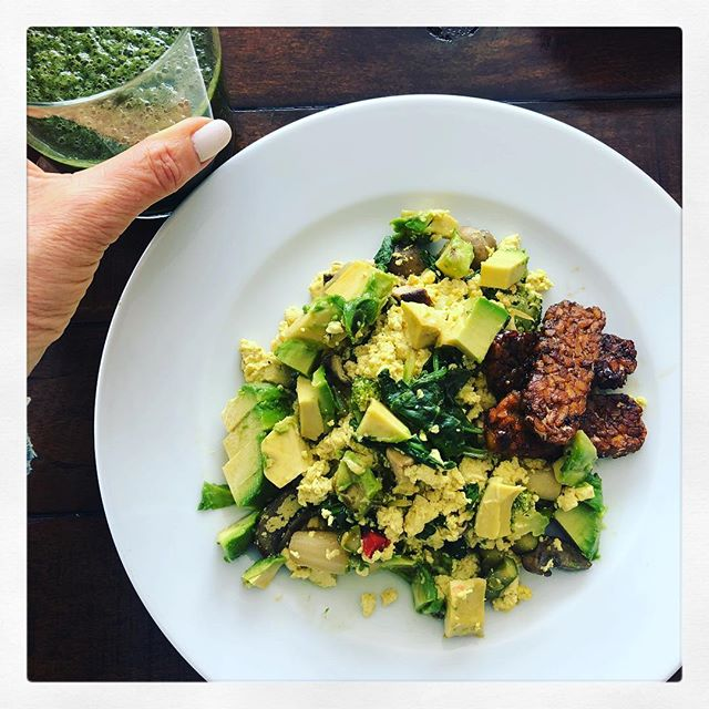 TOFU TURMERIC VEGGIE SCRAMBLE. TEMPEH BACON 🥓! This is the easiest, quickest and heartiest plant based breakfast to whip up when you need something weighty. This scramble can also fit conveniently into a 2 tortillas or 2 collard wraps - In which case add a dollop of salsa 💃🏿 on top! —-RECIPE—- SCRAMBLE INGREDIENTS:  1 container organic tofu, soft is best 1 tsp turmeric  1 C spinach, torn into pieces  1/4 C minced onions, optional Handful of whatever veggies you want to add; mushrooms, peppers, broccoli, etc 1 tsp olive oil 1Tbs coconut aminos  BACON INGREDIENTS : 1 Pkg plain Tempeh, cut into strips.  2 Tbs coconut aminos  GARNISH 1-2 avocado 🥑  PROCESS:  Open tofu and let drain on a paper towel. Place strips of tempeh in heated pan. Drizzle coconut aminos on top until spread evenly. Cook tempeh on medium heat until dark brown and turn each piece as it browns. While tempeh cooks, sauté onions until soft. Add all other veggies and sauté but leave them still a bit crunchy. Break up the tofu with your hands or a fork and add to skillet 🍳. Sprinkle with turmeric and mix well until the tofu resembles scrambled eggs. Season with sea salt and pepper. Plate tofu dish and nestle the tempeh strips close by. Top with avocado. Season with sea salt & pepper. Eat! . . . #tofuscramble #tempeh #breakfast #food #plantbased #vegan #homecook #nutrition #savetheplanet #animalwelfare