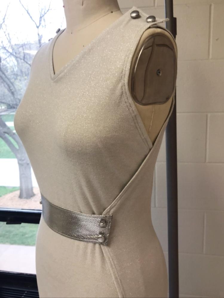 A peek of a wrap jumpsuit, made out of a shimmery silver knit with touches of chrome.